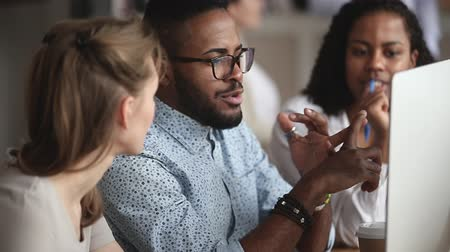 collaborating : Confident smart african american manager in eyeglasses explaining corporate software details to motivated mixed race female colleagues. Smiling multiracial employees listening to leader instructions. Stock Footage