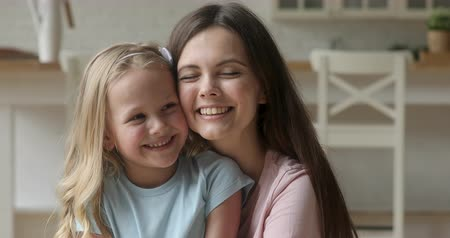 puericultura : Head shot close up smiling young mommy embracing funny blonde adopted daughter. Happy nanny babysitter embracing joyful kid girl. Attractive family of two enjoying tender moment together at home. Stock Footage