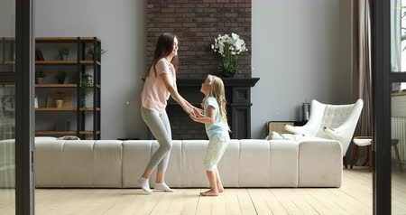puericultura : Full length smiling active young nanny baby sitter holding hands with happy little kid girl, having fun together in living room. Joyful mommy dancing jumping with cute small daughter at home.