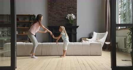 puericultura : Full length overjoyed barefoot little daughter copying mommy s movements in modern living room. Happy young baby sitter nanny teaching small child girl dancing, having fun, enjoying activity at home.