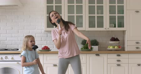 puericultura : Funny family of two holding ladles, singing favorite song together. Artistic young mommy nanny baby sitter and daughter kid girl having fun, using spoon ladles kitchenware as microphones in kitchen. Stock Footage