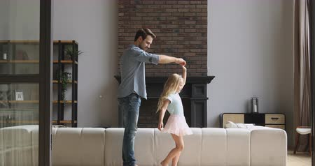 beso : Handsome young father twisting little princess daughter, teaching dancing, kissing girls hand after dance in modern living room. Joyful small child girl enjoying leisure weekend time with dad at home.