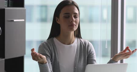 respiração : Calm young businesswoman sitting at table, making mudra gesture, managing stress during workday alone at office. Serene millennial female employee doing yoga breathing exercises, no stress concept.
