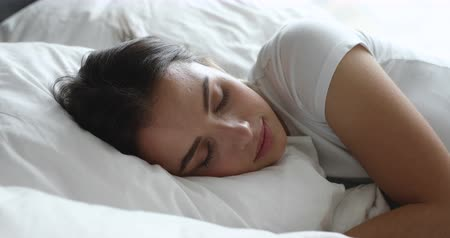 белье : Happy calm millennial woman sleeping in comfortable bed with soft pillow. Carefree young attractive girl enjoying good night rest at home or hotel room, resting in morning, watching good night dreams.