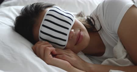 občerstvení : Peaceful young girl wearing night mask, relaxing in comfortable bed. Tranquil happy millennial woman enjoying good night rest on soft pillow and orthopedic mattress alone at home or hotel room.