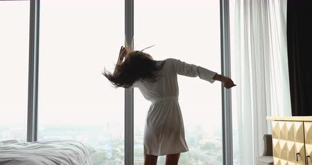 wakeup : Rear back view attractive overjoyed young woman having fun after waking up in morning. Excited millennial girl jumping, dancing to favorite music in front of huge window in modern bedroom at home.