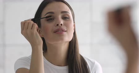 especial : Head shot young attractive woman standing in front of mirror, applying mascara on eyelashes. Successful businesswoman doing make up, getting ready in morning. Smiling lady putting cosmetics on face.