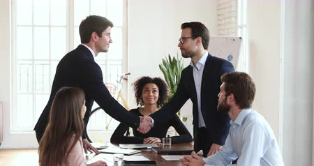 investidor : Two happy successful business partners manager and client wear suit shake hand at board diverse group meeting table express respect gratitude make acquisition deal partnership trust agreement concept