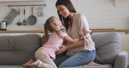 rires : Smiling small adorable child girl playing with mommy on sofa. Happy family of two tickling, having fun together in modern living room. Attractive mother enjoying active time with little daughter.