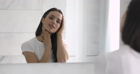 個人的な : Mirror reflection of young happy woman touching soft skin, satisfied with skincare product. Smiling attractive girl putting cosmetics in morning, applying cream foundation, doing make up at home.