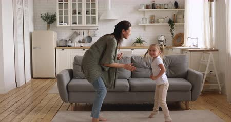 den matek : Full length overjoyed young woman dancing to music barefoot with daughter on carpet in modern studio kitchen living room. Happy little preschool girl having fun laughing with smiling mommy at home.