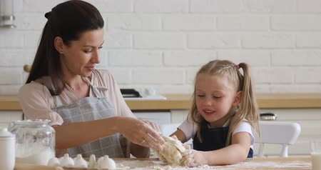 lesgeven : Affectionate smiling 30s woman helping little preschool daughter kneading dough by hands, teaching preparing biscuit. Happy family of two in aprons enjoying baking process together in modern kitchen.