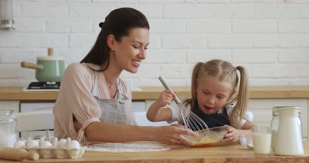 cursus : Happy 30s mother watching small preschool daughter whisking egg mass in glass bottle, teaching preparing homemade bakery in modern kitchen. Smiling adorable child girl helping proud mommy cooking.