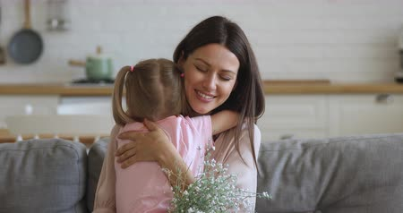 mond : Sincere young mother embracing cuddling little preschool daughter. Happy 30s mom feelings thankful to small kid girl for birthday 8 march international woman s day congratulations, holding flowers.