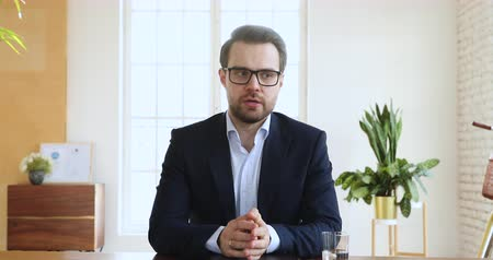 képviselő : Confident businessman ceo wear suit speaking looking at camera in office, male executive manager talking make conference online video chat call job interview recording online training, web cam view