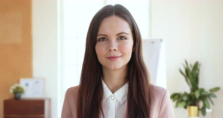 konsultant : Smiling confident young business woman professional looking at camera standing alone in corporate office, happy proud attractive millennial businesswoman female manager intern, close up face portrait Wideo
