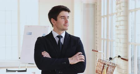 тренер : Successful proud happy young businessman executive wear suit stand arms crossed look away at camera posing in modern office, rich handsome male leader ceo dreaming of new goals opportunities concept Стоковые видеозаписи