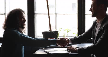collaborating : Side view young african american long-haired man shaking hands with confident caucasian financial advisor salesman real estate agent after negotiating agreement details, sitting together in loft cafe. Stock Footage