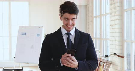 organizatör : Smiling millennial businessman executive wear suit using smartphone apps text message standing in modern office, happy male ceo holding phone tech gadget at work, mobile business technology concept Stok Video