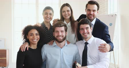 etnia africano : Six happy friendly professional multicultural team business people embracing bonding together in office look at camera, young smiling multiethnic corporate staff group portrait, teamwork concept Stock Footage