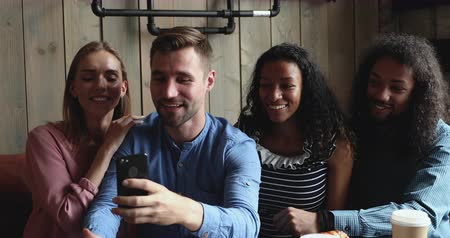 写真 : Happy handsome caucasian guy holding smartphone, showing funny photo editing application to mixed race smiling best friends, sitting in cafe. Overjoyed diverse young people having fun together.