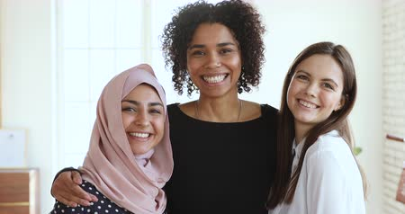etnia africano : Three multicultural smiling young women friends embracing looking at camera, happy beautiful diverse african, indian muslim and caucasian ladies bonding together indoors, close up video portrait Stock Footage