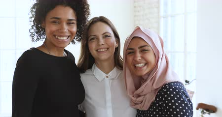 multikulturális : 3 cheerful friendly diverse millennial women bonding laughing looking at camera, three happy young ladies having fun embracing in office, closeup portrait, multicultural unity friendship concept