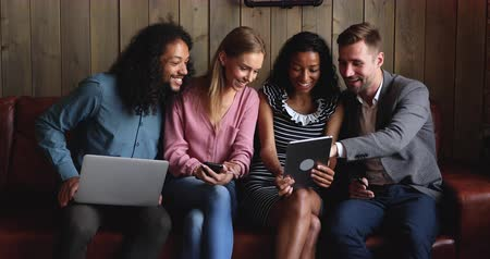 dojemný : Happy young african american woman showing funny content to excited mixed race friends on digital tablet. Smiling multiracial students sitting on couch with different gadgets, having fun together.