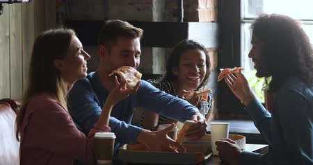 общаться : Overjoyed young multiracial friends sitting in modern public place, sharing takeaway pizza from cardboard box, enjoying leisure lunch time together. Happy mixed race people having fun, eating food.