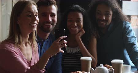 Smiling caucasian woman holding mobile phone, taking selfie with happy mixed race friends together in cafe. Excited multiracial people recording funny video, posing for photo in public place.