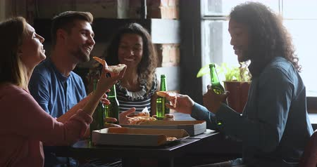 etnia africano : Happy african american guy holding bottle of beer and pizza slice, telling funny joke storytelling to laughing multiracial friends. Excited mixed race people enjoying conversation while sharing lunch. Stock Footage