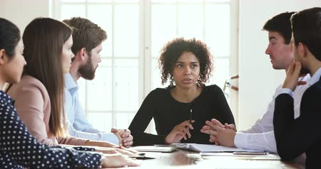 Confident african american businesswoman leader explaining corporate strategy speak at diverse group board meeting training instructing professional team discuss work plan at office briefing table