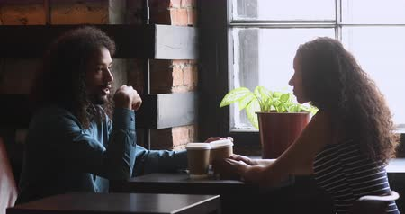multirracial : Young african american man and woman sitting in front of each other at wooden table, chatting in cafe. Millennial mixed race friends interacting communicating talking sharing news at meeting.