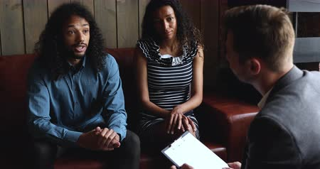 dialog : Upset young african ethnicity married couple sitting on cozy couch, meeting psychologist. Unhappy mixed race spouses sharing family problems on consultation with professional, marriage counseling.