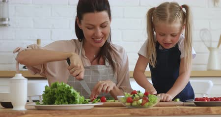 Happy pleasant mommy teaching little cute daughter cutting fresh vegetables for salad. Bonding affectionate family of two in aprons enjoying preparing healthy meal together in modern kitchen.