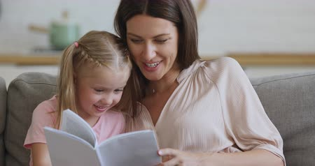 общаться : Focused young mother holding paper book, reading interesting story fairytale to smiling interested small preschool daughter. Smiling small kid girl learning letters with babysitter nanny on couch.