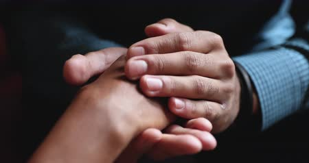 overcome : Close up young african american man holding female hands, demonstrating support. Mixed race spouses reconciling after misunderstanding. Biracial husband comforting wife, overcoming problems together. Stock Footage