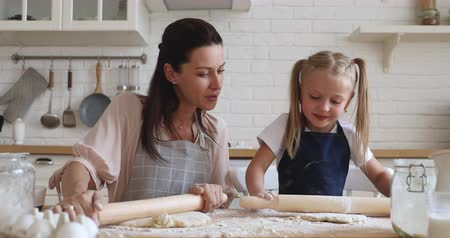 cursus : Happy 30s woman teaching little preschool daughter flattening dough. Smiling family of two preparing homemade bakery food together in modern kitchen. Pleasant mommy showing how to use rolling pin.