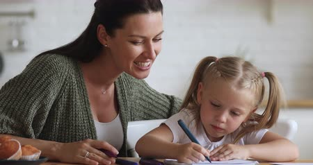desenvolver : Smiling young woman sitting at table with cute preschool daughter, drawing together in album. Pleasant baby sitter nanny teaching little child girl writing letters with colorful felt-tip pens at home.