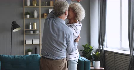 Happy carefree elderly senior grandparents dancing waltz in modern living room, loving old husband laughing holding mature wife enjoying retirement lifestyle talking in slow dance having fun at home