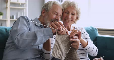 dialog : Happy grandparents family couple having fun helping knitting scarf together at home, smiling elderly senior husband grandpa learning knit with old wife grandma teaching hobby craft sitting on sofa Wideo