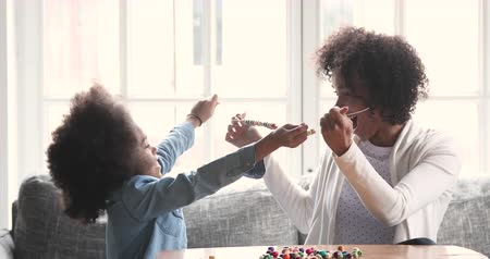 etnia africano : Happy excited african american parent mom babysitter and cute small child daughter making necklace giving high five having fun playing together enjoying leisure games sit on couch in living room Stock Footage