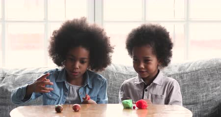 Two cute little african american sister and brother playing playdough together on table in living room, 2 mixed race kids having fun with plasticine clay at home, children creative activity concept