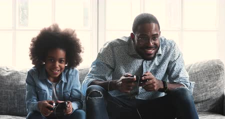 playstation : Happy young dad and cute child kid daughter gamers winners holding joysticks controllers playing winning video game give high five sit on sofa celebrating victory enjoying leisure activity at home