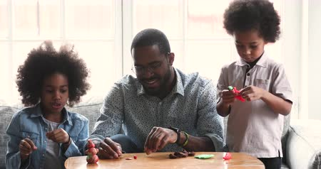 omini : Two cute african american children preschoolers and young adult parent dad teacher babysitter sculpting toys from playdough playing together with plasticine sit on sofa enjoy leisure activity at home