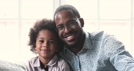 milující : Cheerful smiling african american young adult father and little cute kid son looking at camera laughing at home, mixed race family dad child boy happy faces sit on sofa bonding, closeup portrait