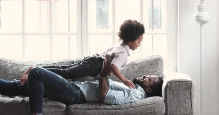 Loving african american dad holding lifting cute preschool child son playing active game pretend airplane flying in fathers arms enjoying good time together with daddy at home on sofa in living room