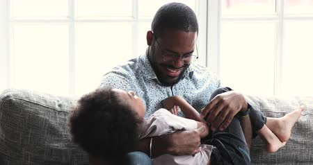 Funny happy young adult african american daddy tickling cute small son relaxing on sofa, loving ethnic father having fun laughing playing with little adorable cuddling together sit on couch at home
