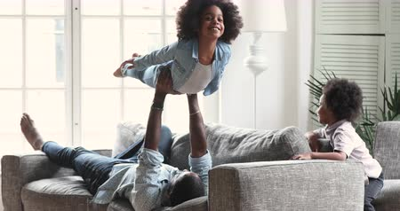 Happy afro american family play enjoy activities in living room, african dad lift cute small daughter up in air while little child son having fun at home, father with two children lifestyle at home Vídeos