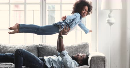 Happy cute afro american girl playing plane game laughing having fun with young father, happy dad lifting small child daughter up fly enjoying family leisure airplane game relaxing on sofa at home